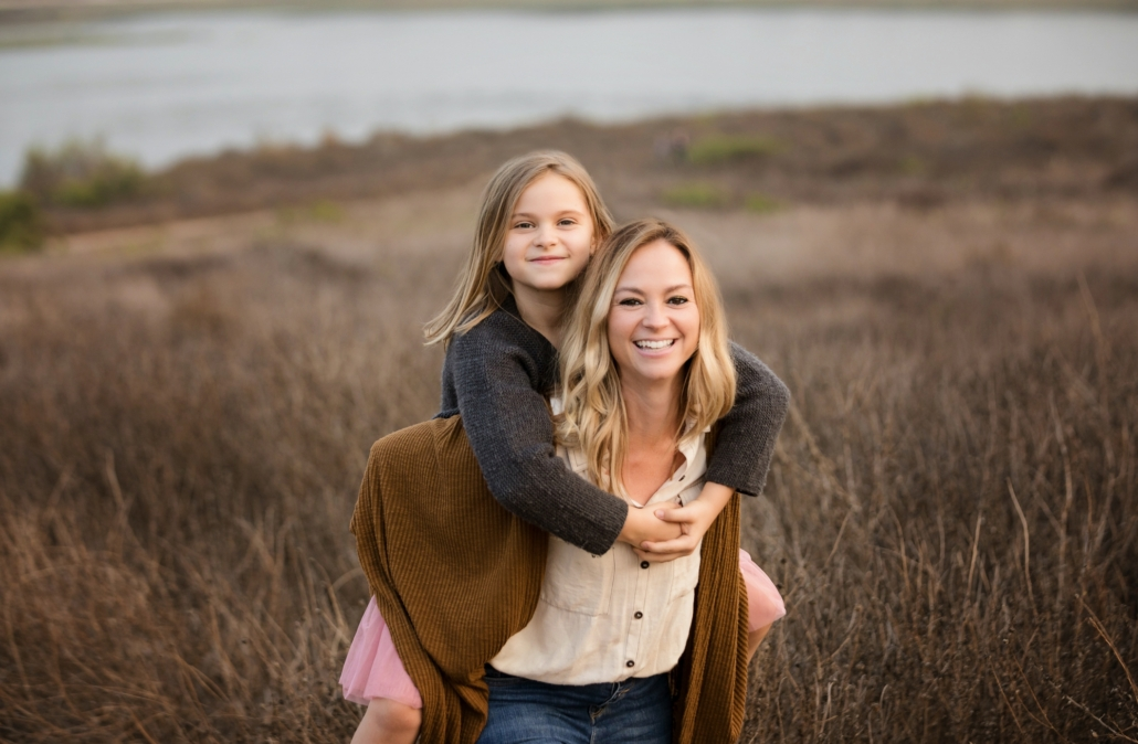 A mom giving her daughter a piggy back ride at a Newport Beach family photo shoot