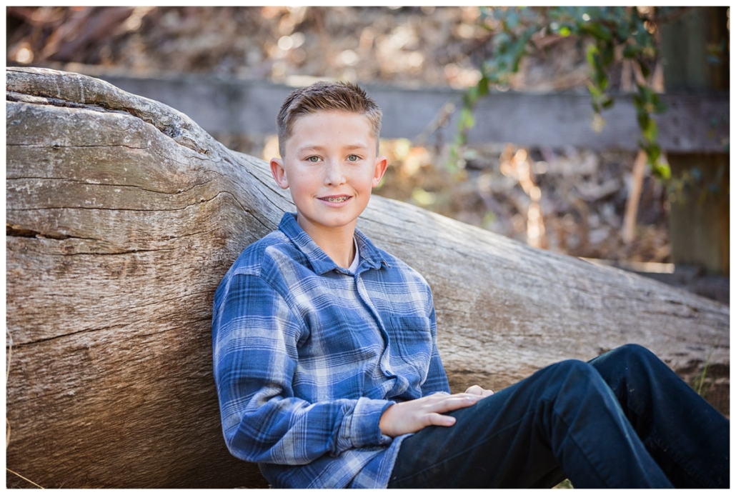 Family portrait session in Orange County. Photograph of the youngest son in the family leaning on a fallen log.
