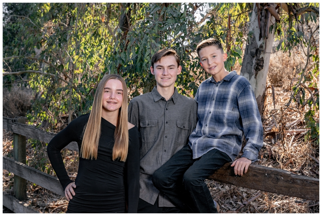 Siblings leaning on a fence for family picture in Orange County