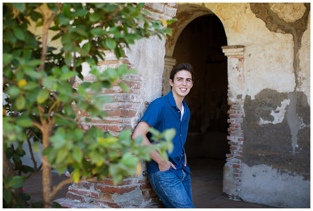 High School senior guy posing in an archway in the Mission in San Juan Capistrano