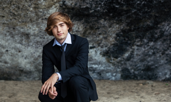 High School Senior guy photographed at the beach in a suit.